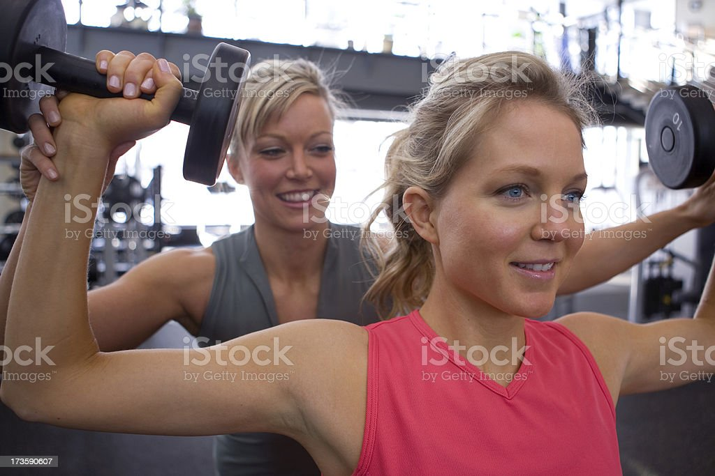 Personal trainer spotting a woman doing shoulder presses royalty-free stock photo