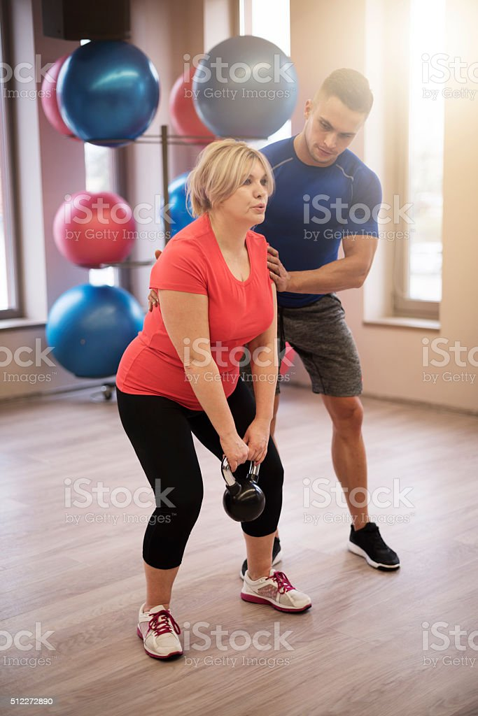 Personal trainer supporting mature woman stock photo