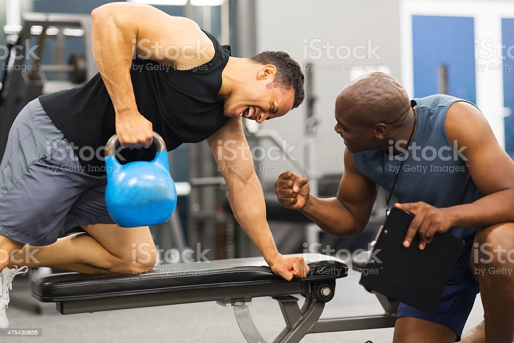 personal trainer training man with kettle bell stock photo