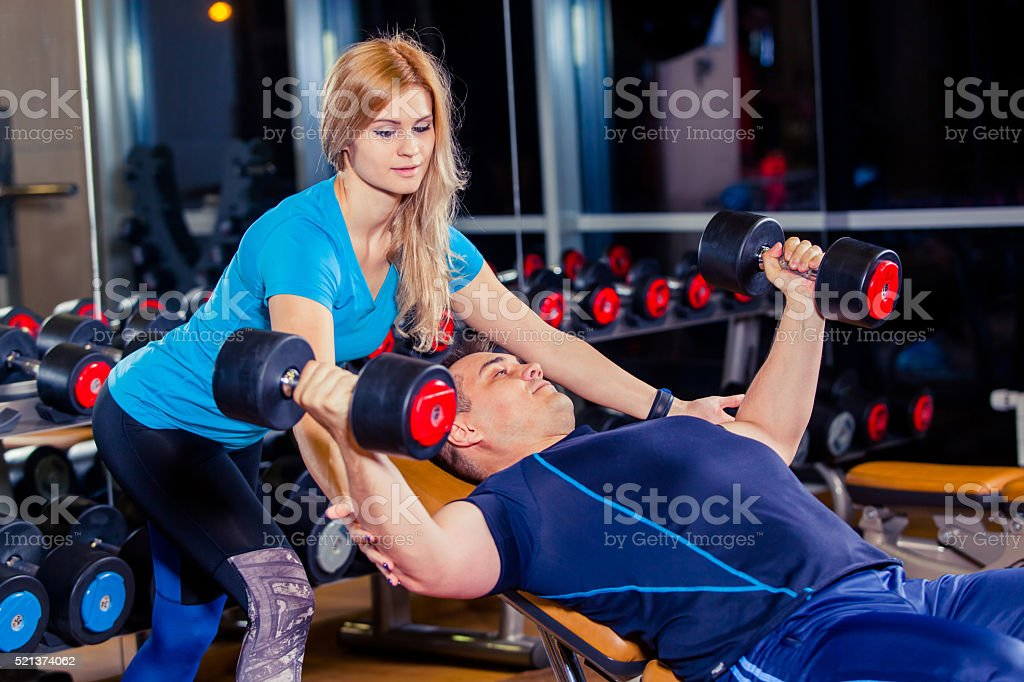 Personal trainer woman helping men working with heavy dumbbells stock photo