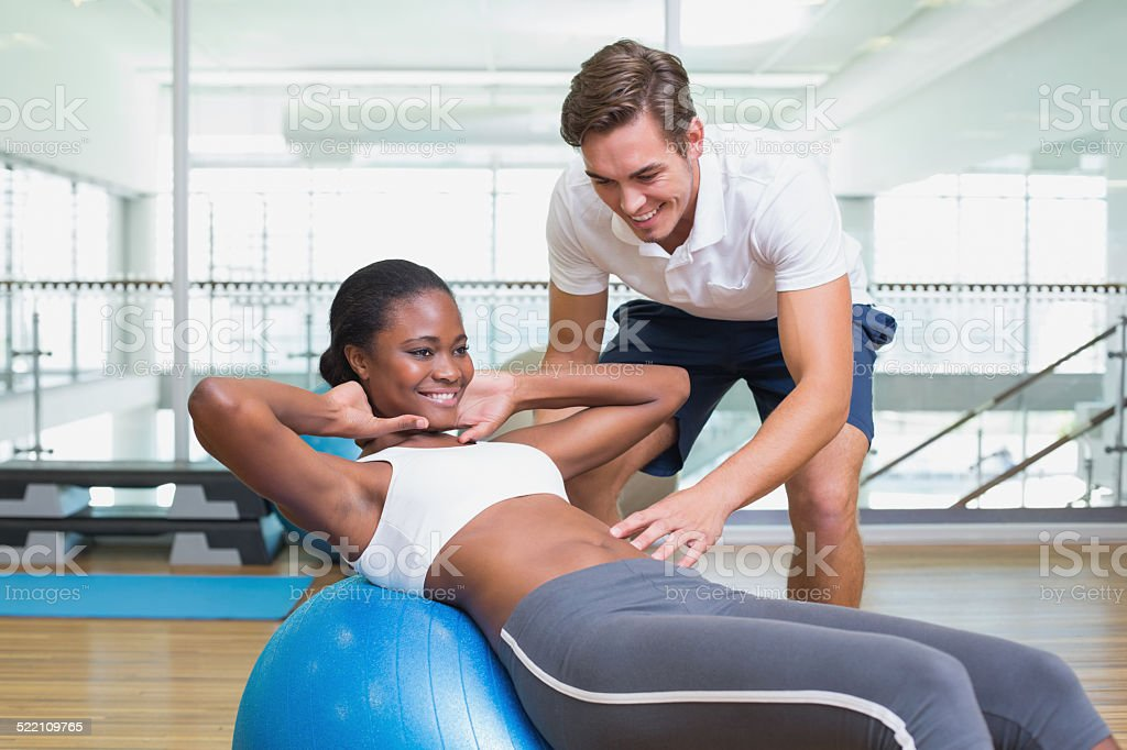 Personal trainer working with client on exercise ball stock photo
