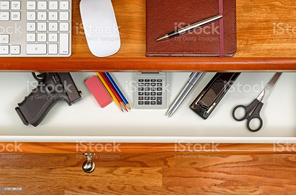 Personal weapon in work desk stock photo