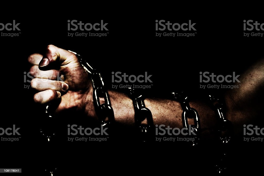 Person's Arm Wrapped in Chains, Low Key stock photo