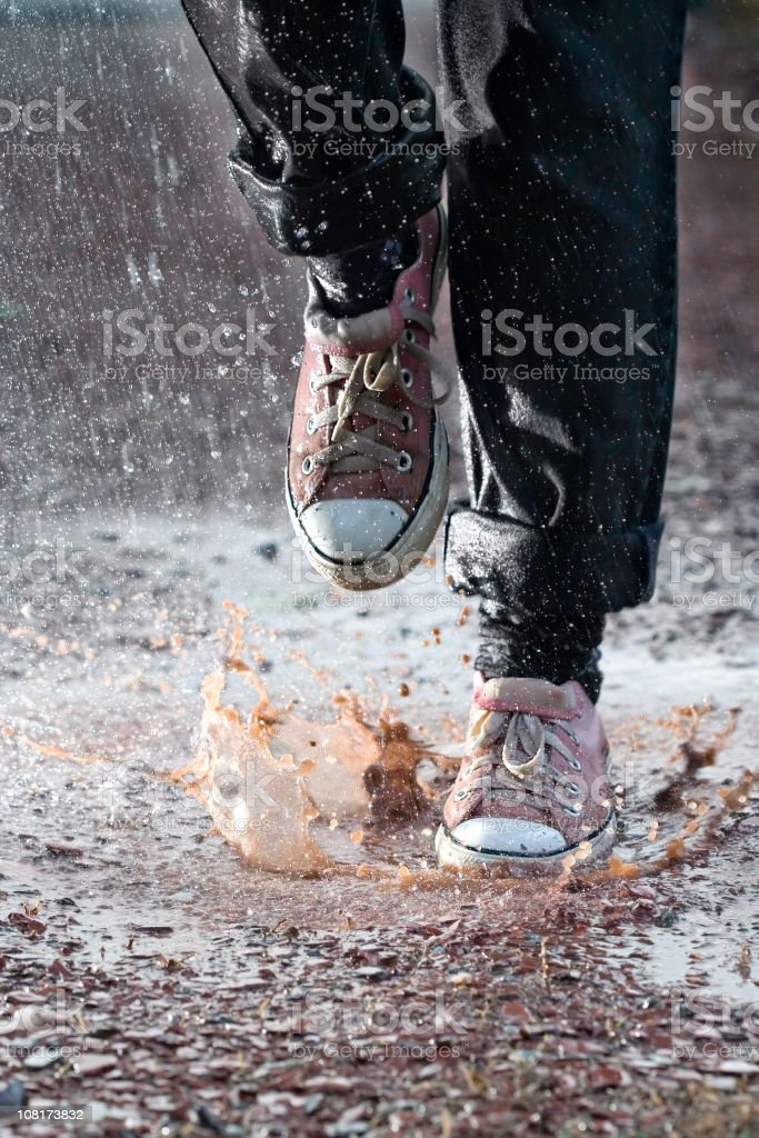 Person's Feet in Sneakers Running Through Muddy Puddle royalty-free stock photo