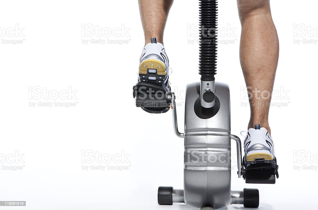 Persons feet while using stationary bike on white background stock photo