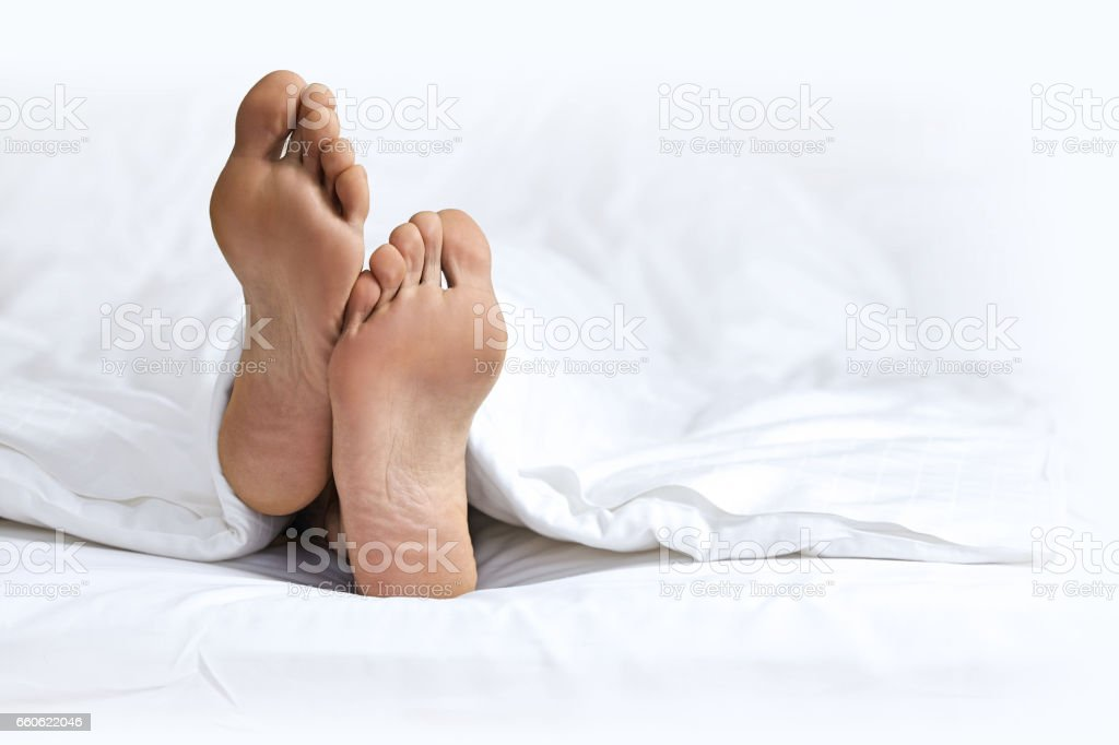 Person's foot in bed stock photo