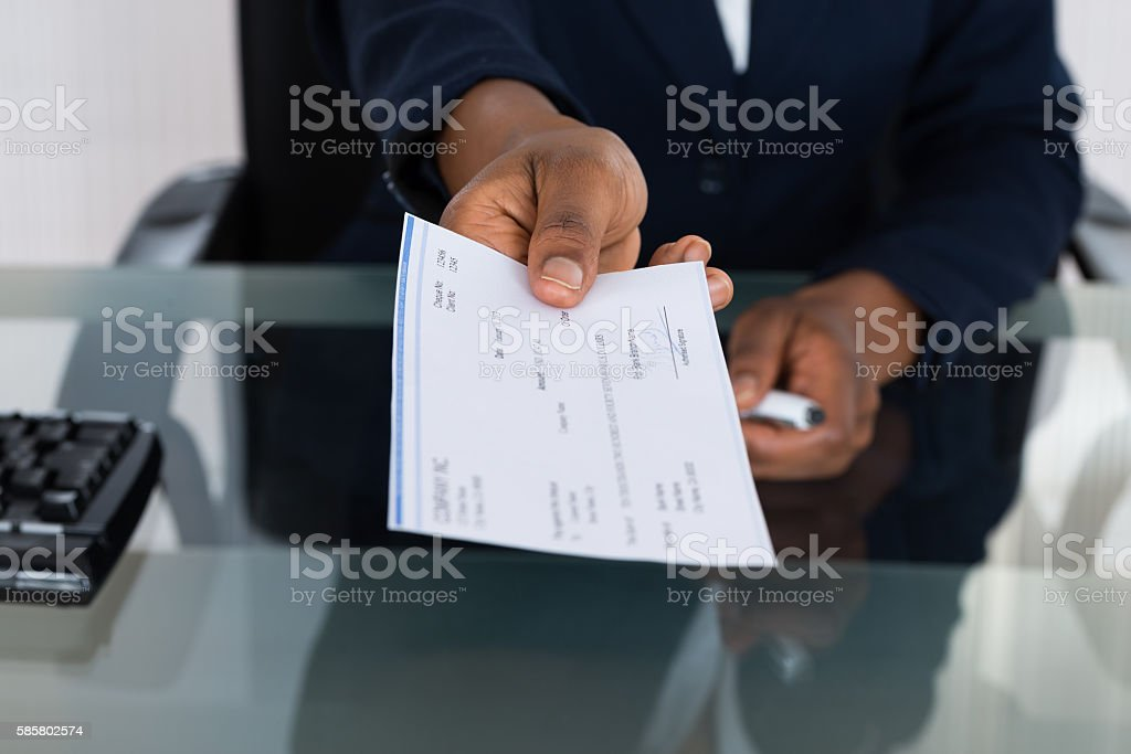 Person's Hand Giving Cheque stock photo