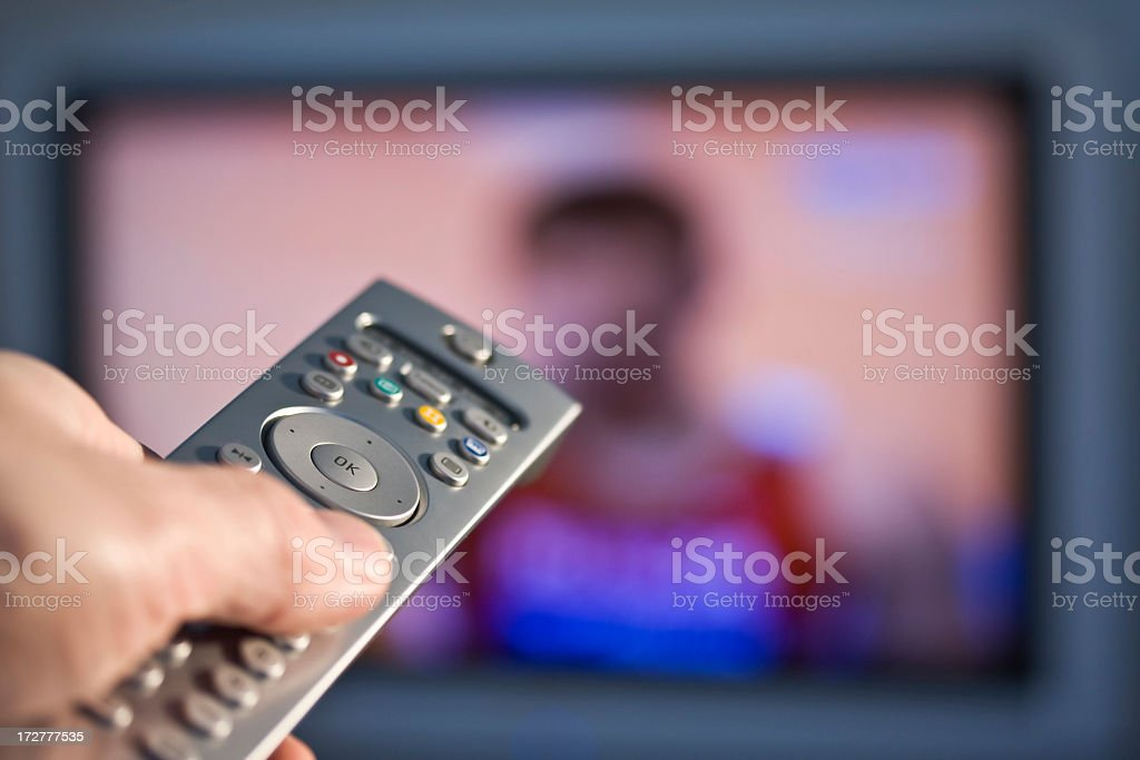 A person's hand holding a remote control royalty-free stock photo