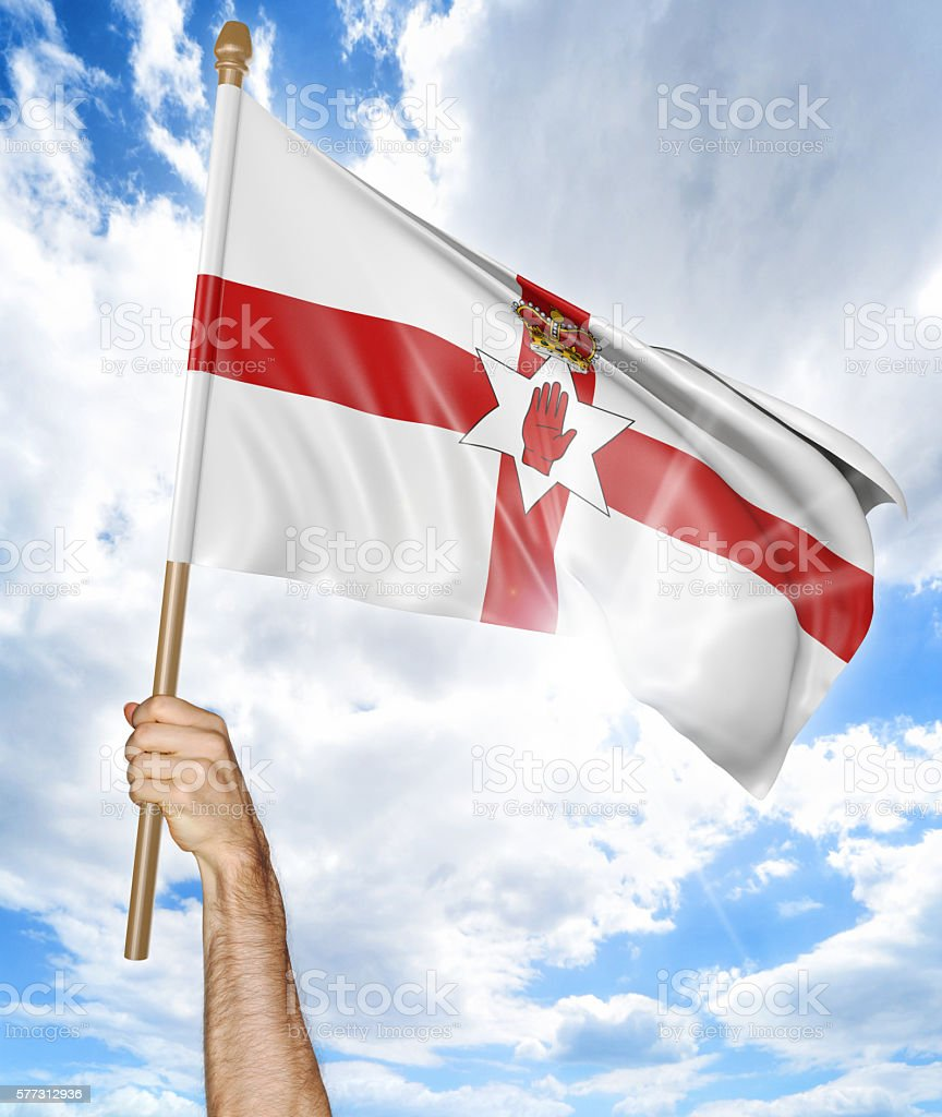 Person's hand holding Northern Ireland national flag and waving it stock photo