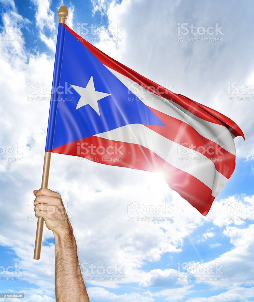 Person's hand holding Puerto Rican national flag and waving it stock photo