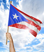 Person's hand holding Puerto Rican national flag and waving it
