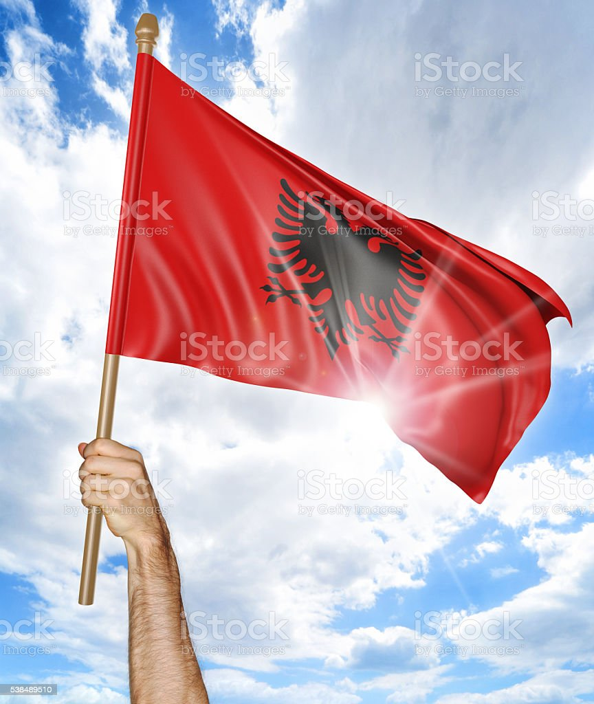 Person's hand holding the Albanian national flag and waving it stock photo