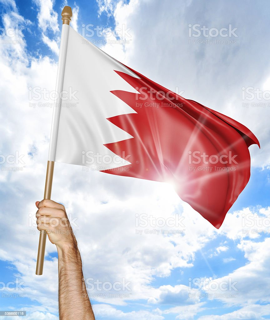 Person's hand holding the Bahraini national flag and waving it stock photo