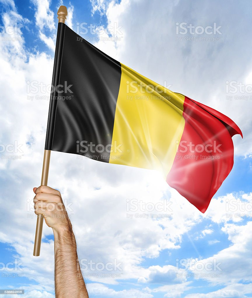 Person's hand holding the Belgian national flag and waving it stock photo