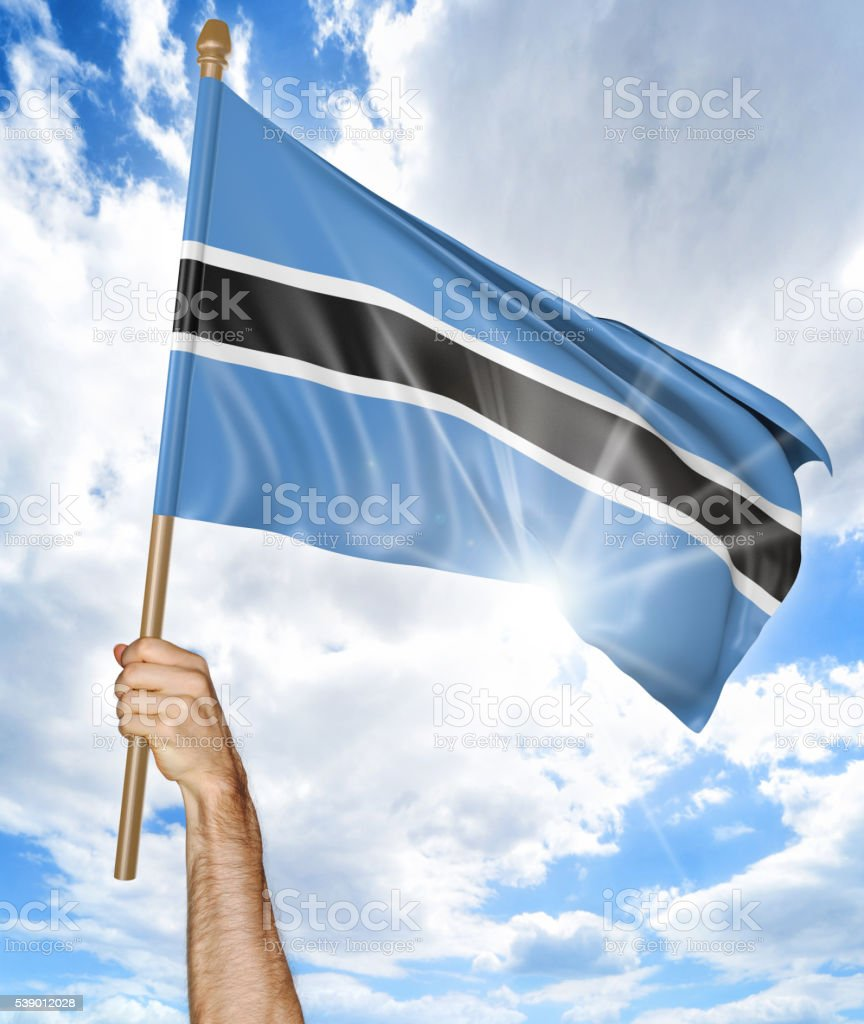 Person's hand holding the Botswana national flag and waving it stock photo