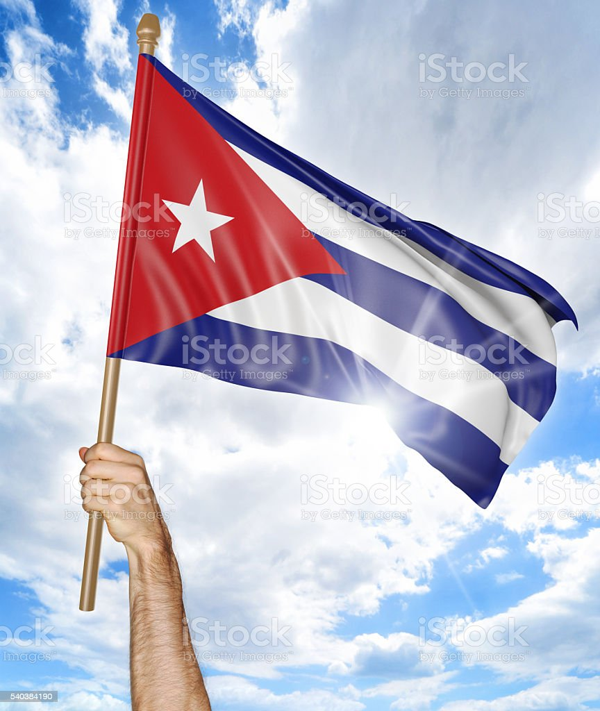 Person's hand holding the Cuban national flag and waving it stock photo