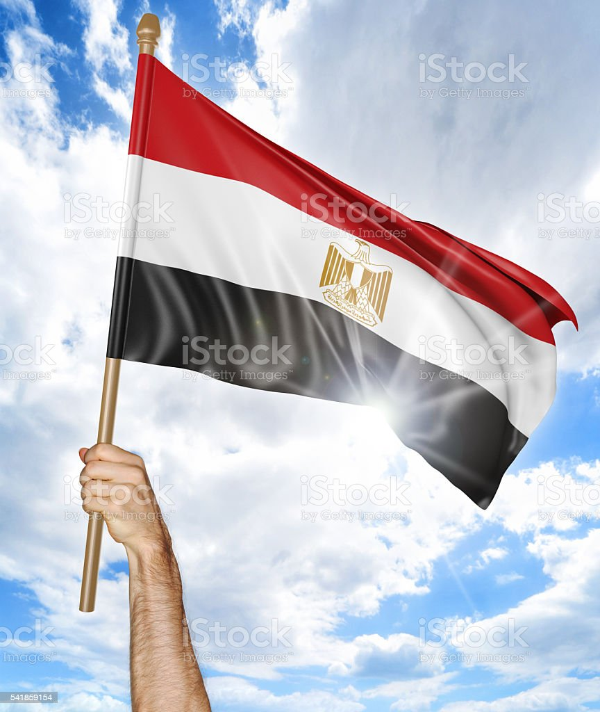 Person's hand holding the Egyptian national flag and waving it stock photo