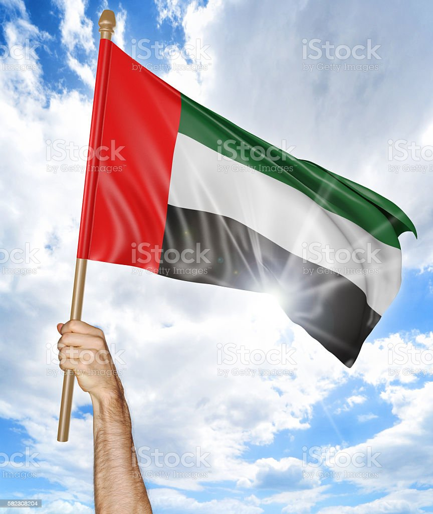 Person's hand holding the Emirati national flag and waving it stock photo
