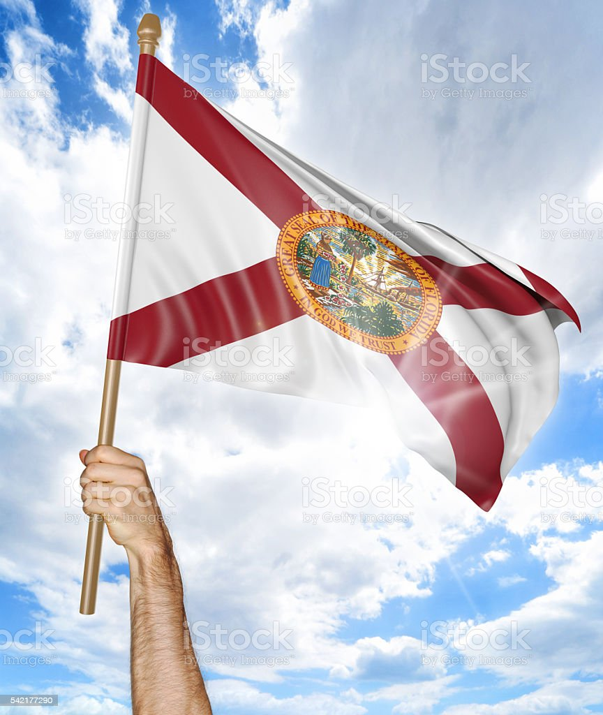 Person's hand holding the Florida state flag and waving it stock photo