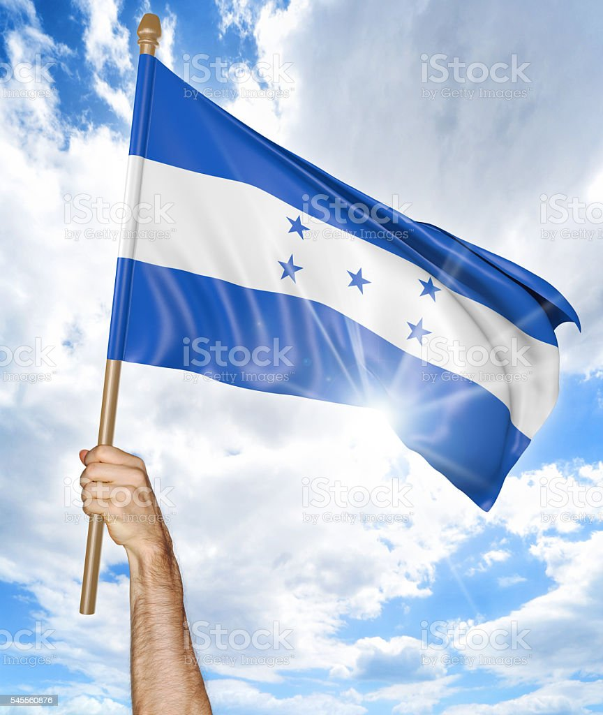 Person's hand holding the Honduran national flag and waving it stock photo