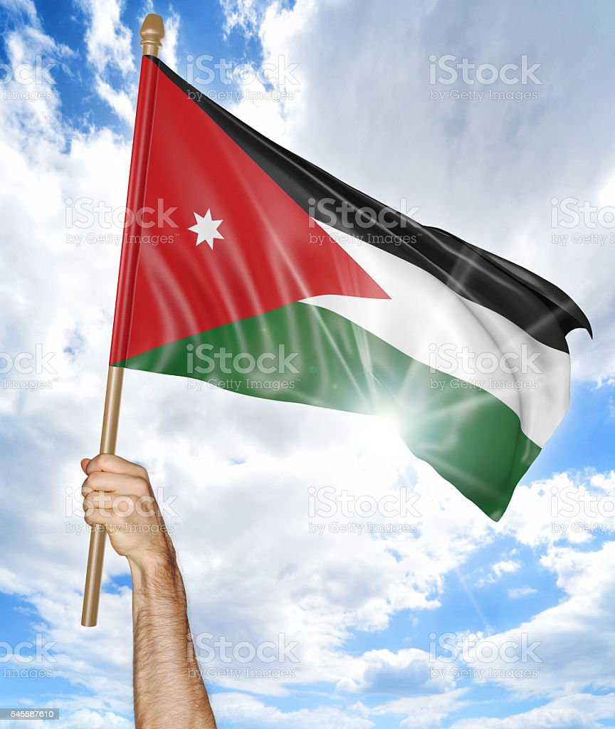 Person's hand holding the Jordanian national flag and waving it stock photo