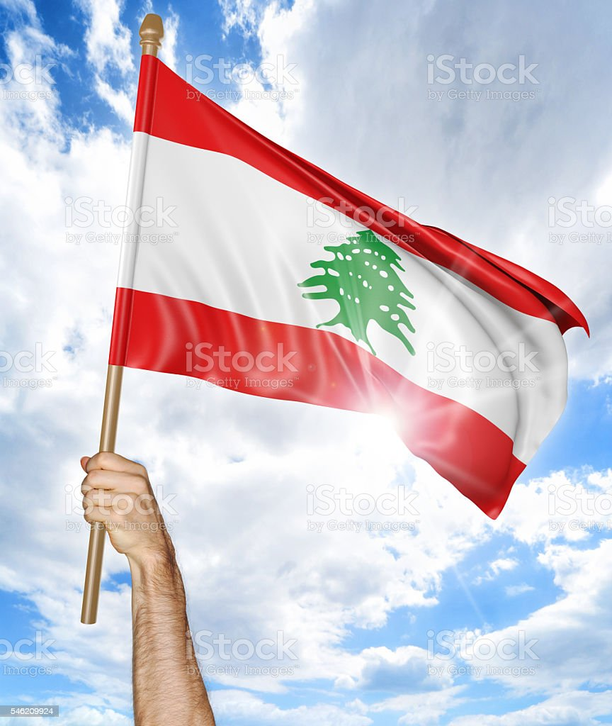 Person's hand holding the Lebanese national flag and waving it stock photo