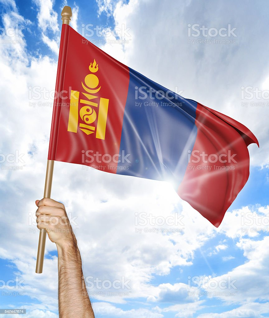 Person's hand holding the Mongolian national flag and waving it stock photo