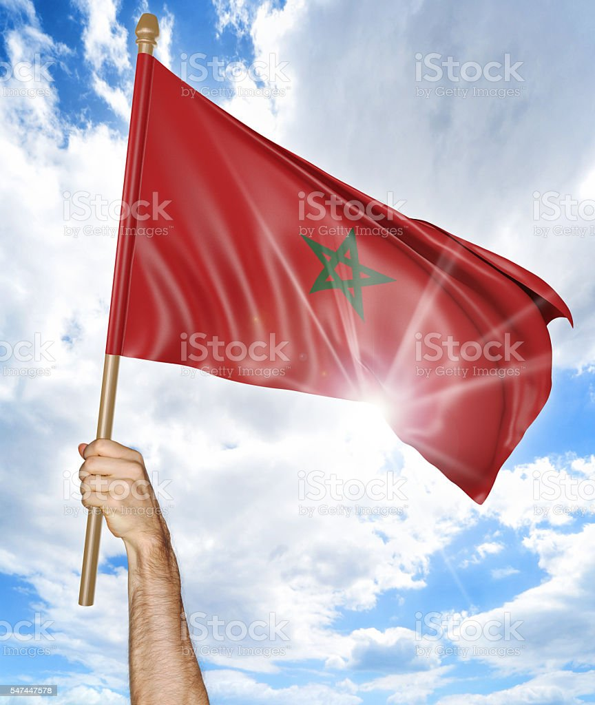 Person's hand holding the Moroccan national flag and waving it stock photo
