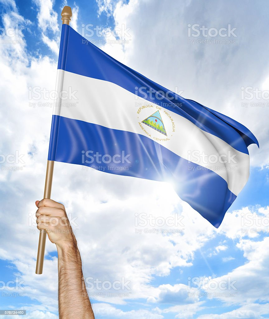 Person's hand holding the Nicaraguan national flag and waving it stock photo