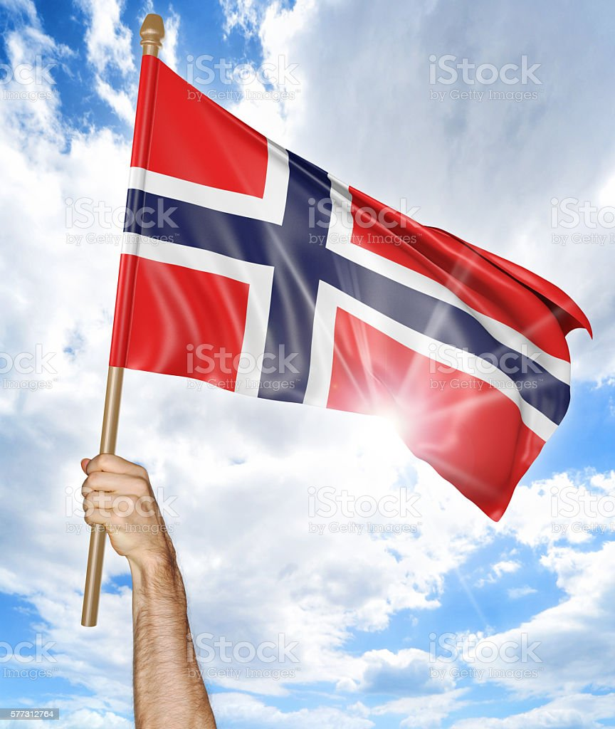 Person's hand holding the Norwegian national flag and waving it stock photo