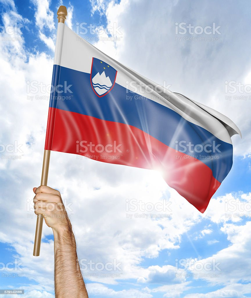 Person's hand holding the Slovenian national flag and waving it stock photo