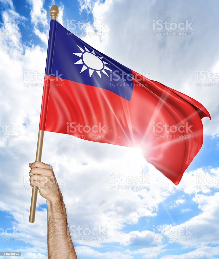 Person's hand holding the Taiwanese national flag and waving it stock photo