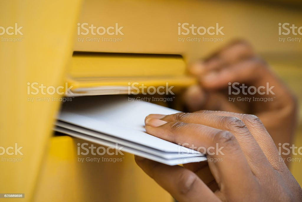 Person's Hand Inserting Letter In Mailbox stock photo