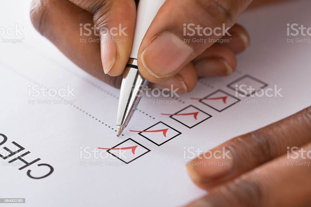 Person's Hand Marking On Checklist Form With Red Pen stock photo