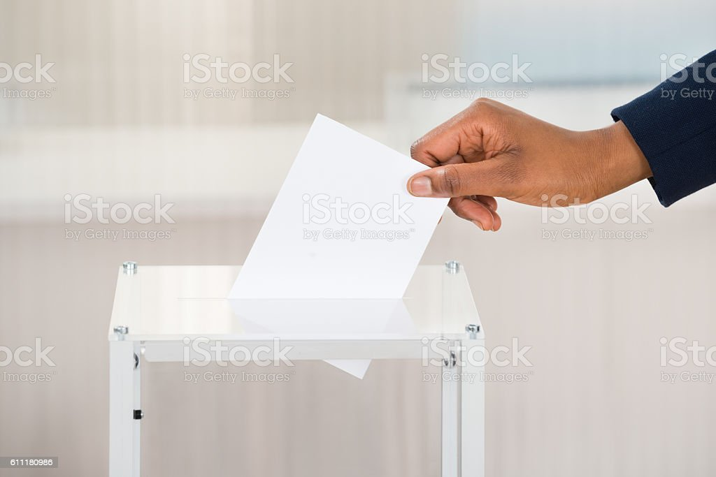 Person's Hand Putting Ballot In Box stock photo