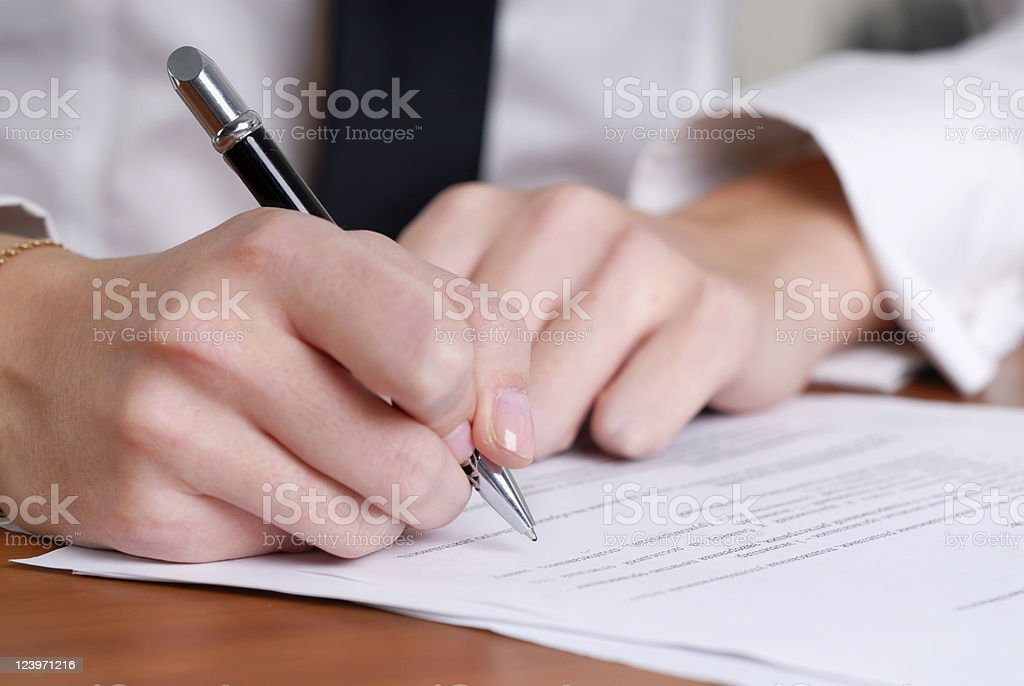 person's hand signing an important document stock photo