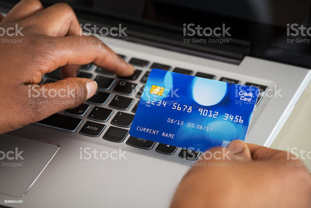 Person's Hand Using Debit Card While Shopping Online stock photo