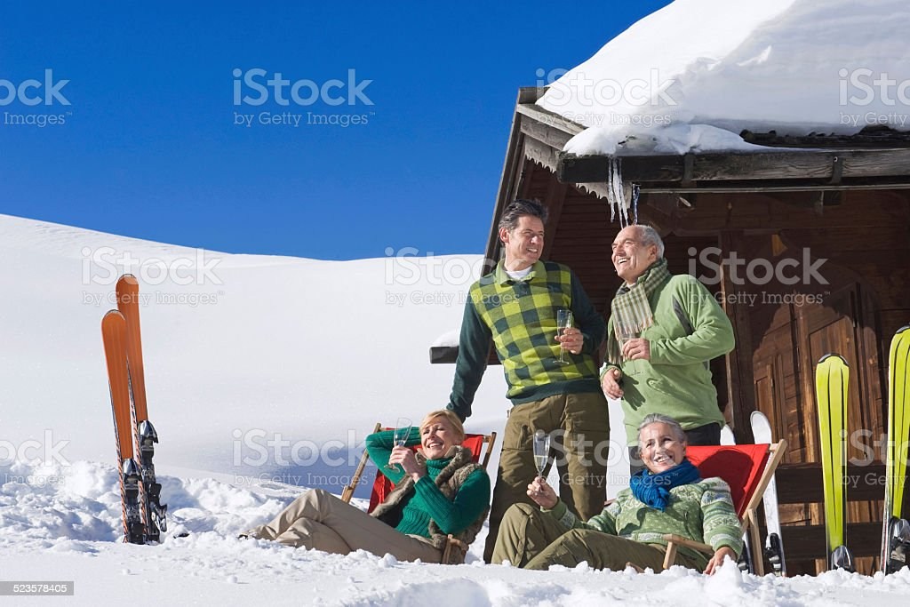 Persons in front of log cabin, holding champagne glasses stock photo