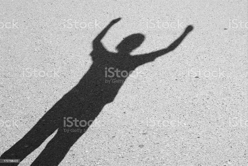 A persons shadow with arms raised royalty-free stock photo