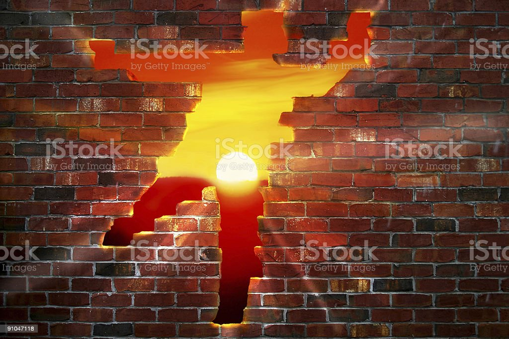 A person-shaped hole in a brick wall with the sun setting stock photo