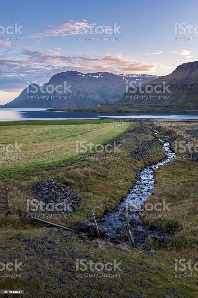 Perspective line of small stream during sunset in fjord Iceland stock photo