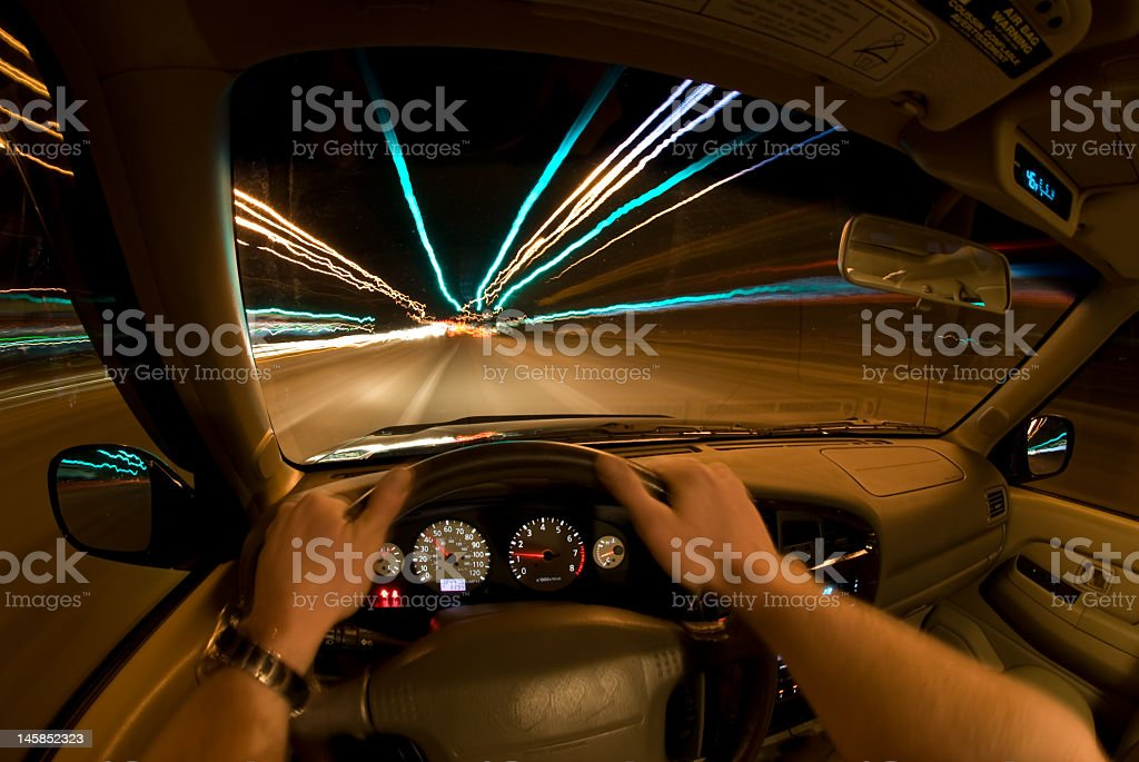 Perspective of driver inside car speeding at night stock photo