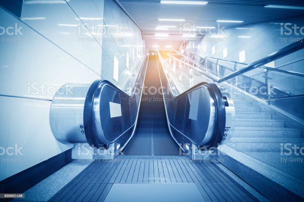Perspective of two empty escalators with illuminated sides stock photo