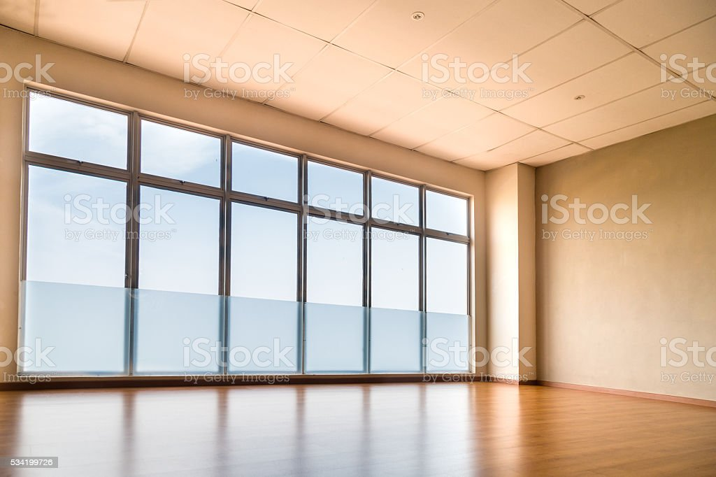 Perspective view of empty studio illuminated with light from win stock photo