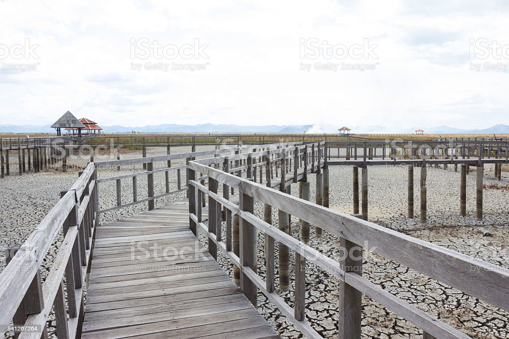 perspective wooden bridge with dry earth and cracked ground texture stock photo