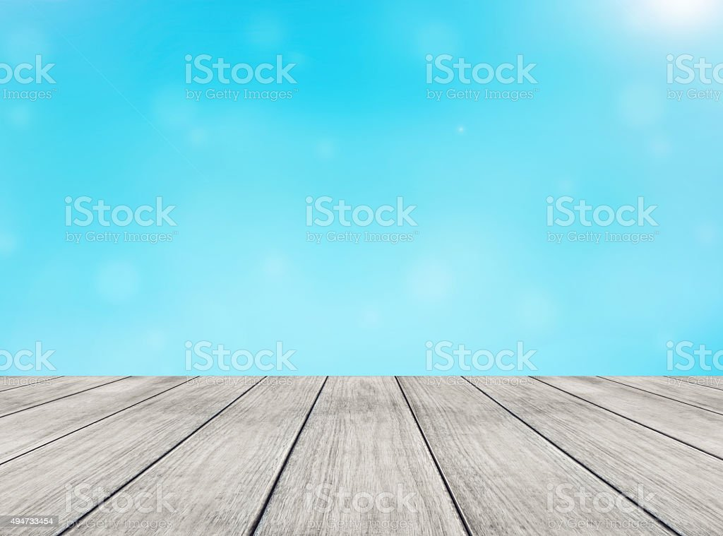 perspective wooden floor and blue sky blurred background stock photo