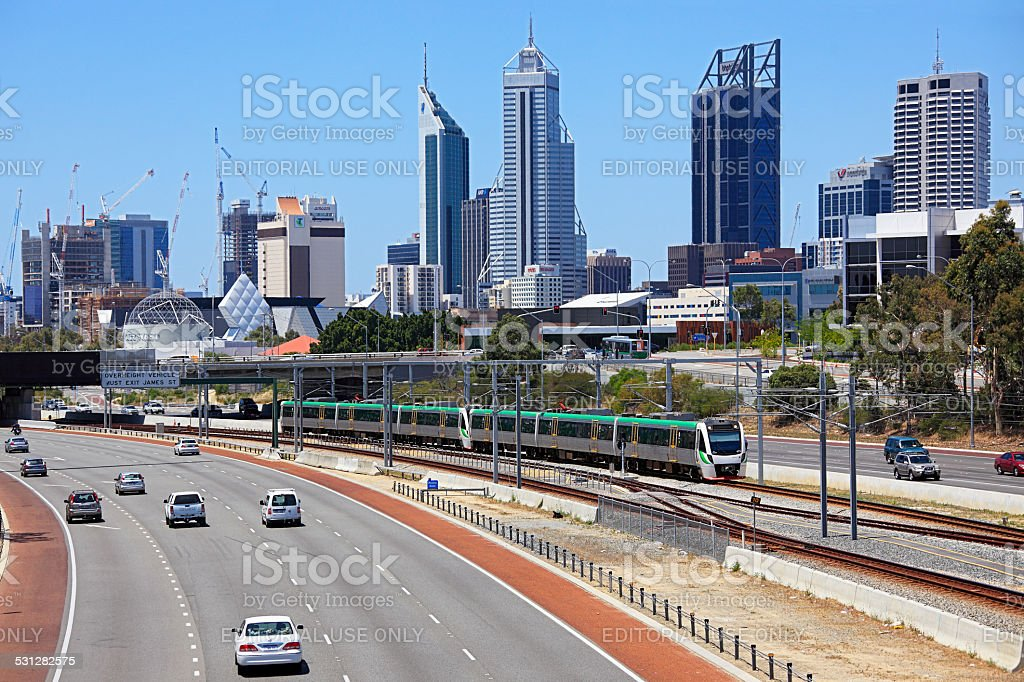 Perth cityscape with electric train running down freeway. stock photo