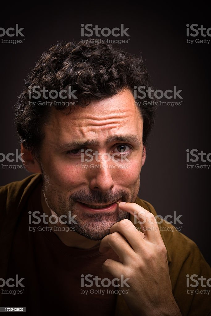 Perturbed man with finger on mouth stock photo