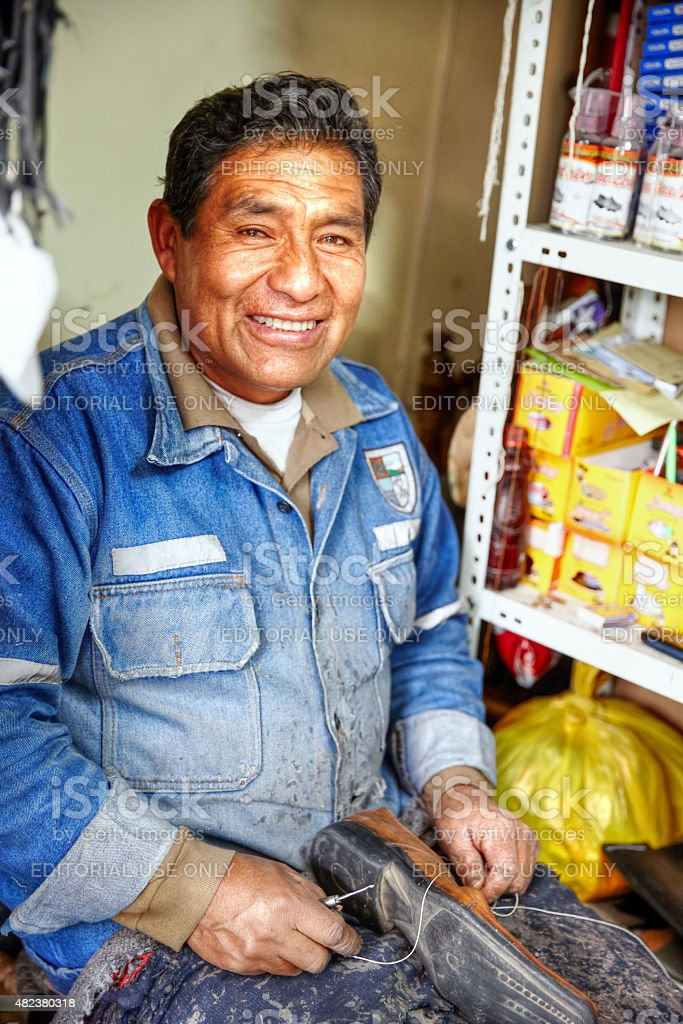 Peruvian cobbler at work on his market stall stock photo