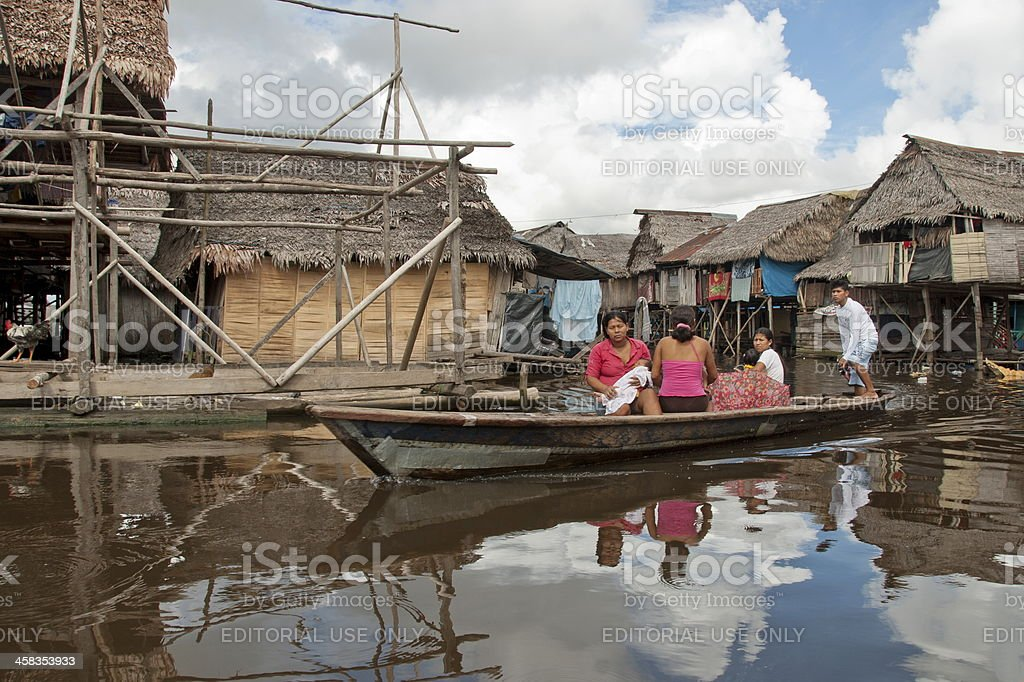 Peruvian family floating on water in Iquitos stock photo
